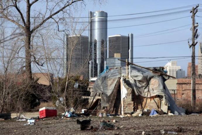 This is a picture of a shelter someone who was homeless has created to sleep in. The background picture is of Detroit, the Renaissance Center. In the winter, 'tent cities' are created in stretches of open fields. Our winters get bitter. Down to -20 for our windchills, if not colder. Sometimes the Warren mayor will pay for rooms for the homeless if it is so cold that bodies of homeless people are being found outside.