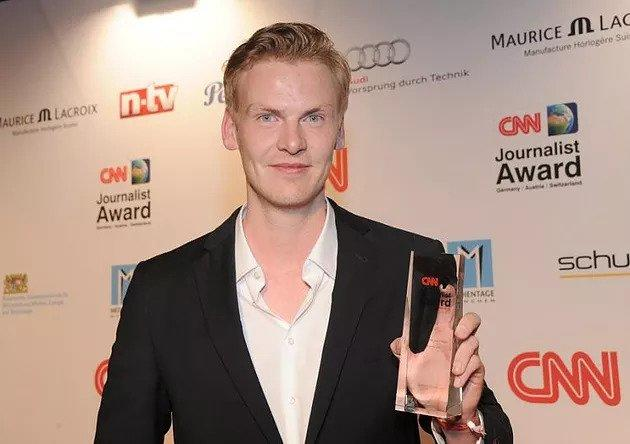 """Claas Relotius holding his CNN's 2014 """"Journalist of the year"""" award."""