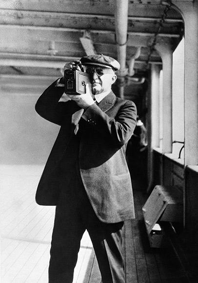 George Eastman, founder of Kodak, using a Kodak box camera, loaded with roll film