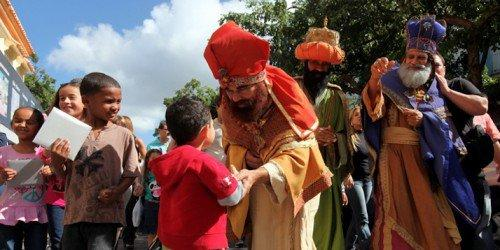 kids getting gifts from people dressed like the 3 wise men in La Fiesta de Reyes Isabelinos