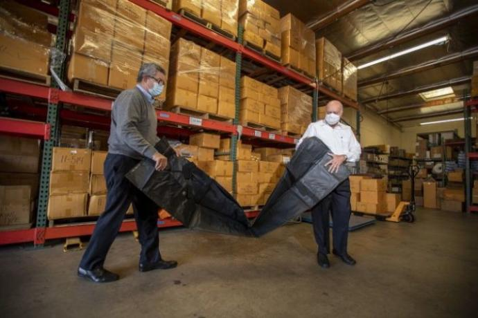 Workers unpack a body bag