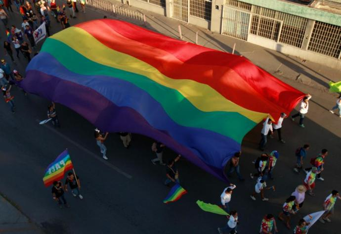 LGBTQ+ members holding a large flag during a march
