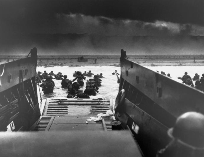 While under attack of heavy machine gun fire from the German coastal defense forces, these American soldiers wade ashore.