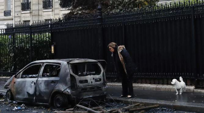 A woman looks at her charred car the day after a demonstration, near the Arc de Triomphe, in Paris.