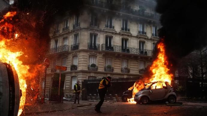 Protesters walk by burning cars during clashes with riot police on the sideline of a protest of Yellow vests