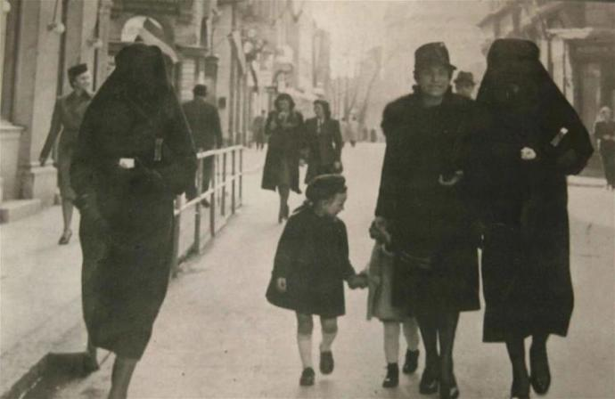 A Muslim woman protects a Jewish woman by covering her Star of David with her veil.