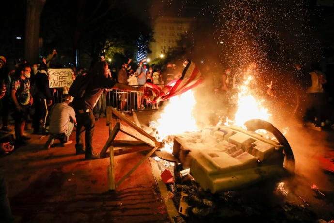 Demonstrators start a fire as they protest the death of George Floyd near the White House in Washington.