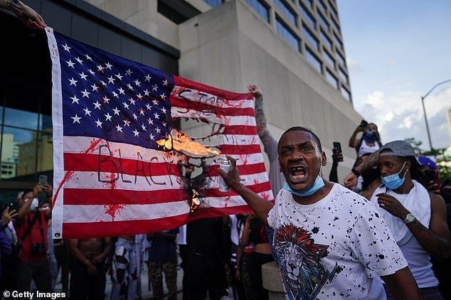 Atlanta: Protesters burn an American flag outside the CNN Center on Friday