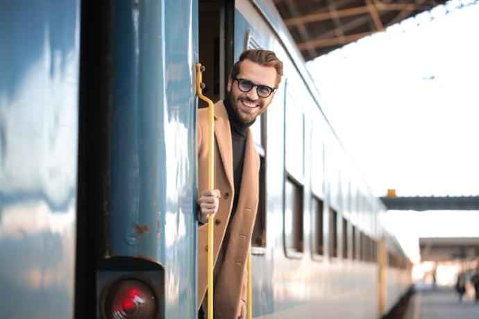 What is this man leaning out of the train so happy about?
